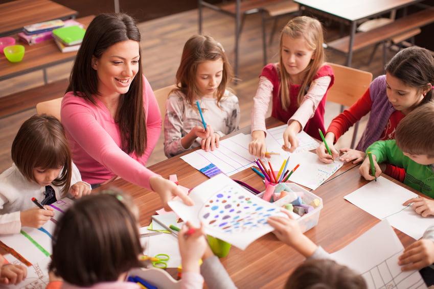 Nauczyciel z dziećmi siedzą przy stole i rysują.