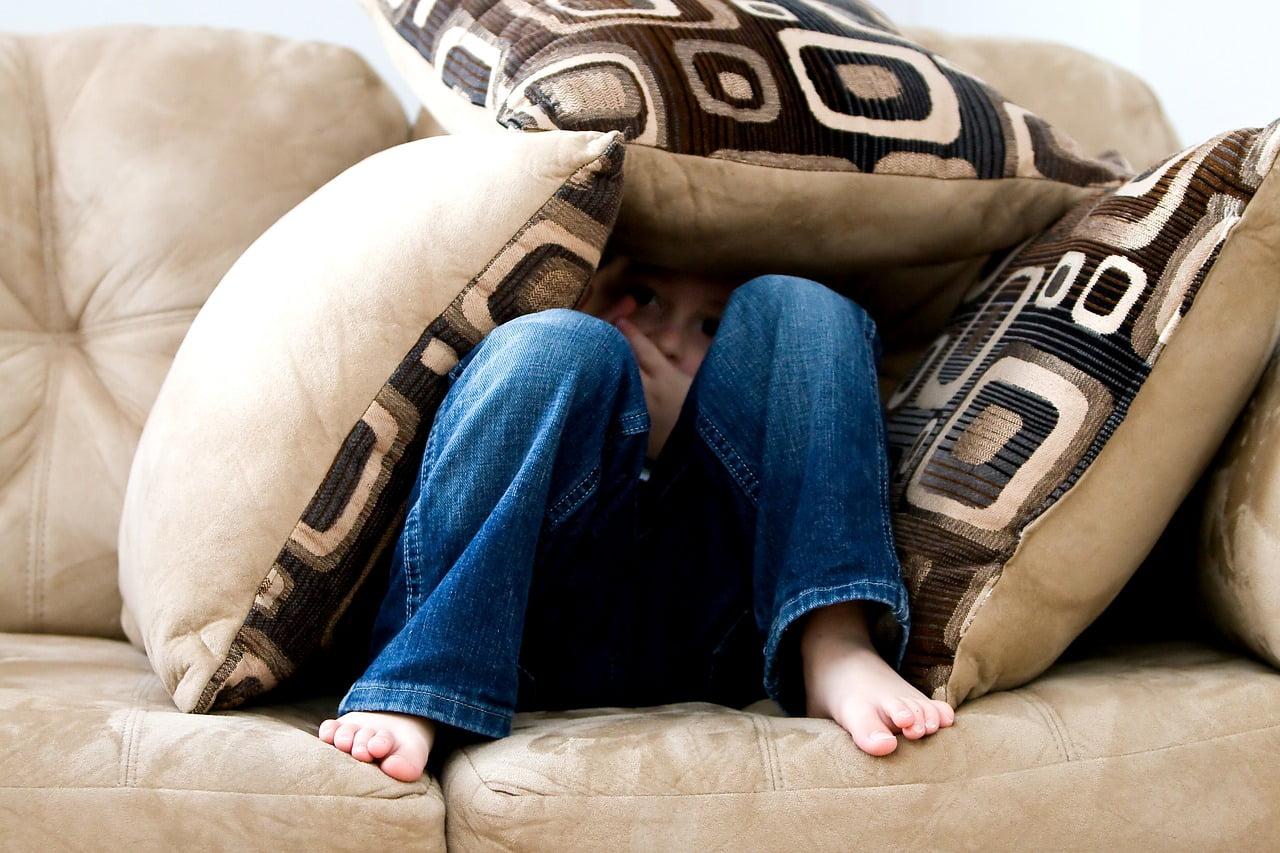 Dziecko siedzi na kanapie, chowa się za poduszkami