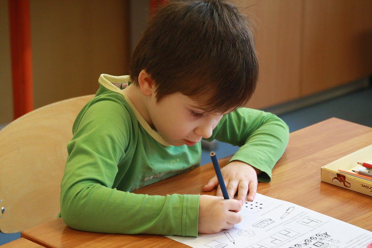 Chłopiec siedzi w ławce i uzupełnia kartę pracy