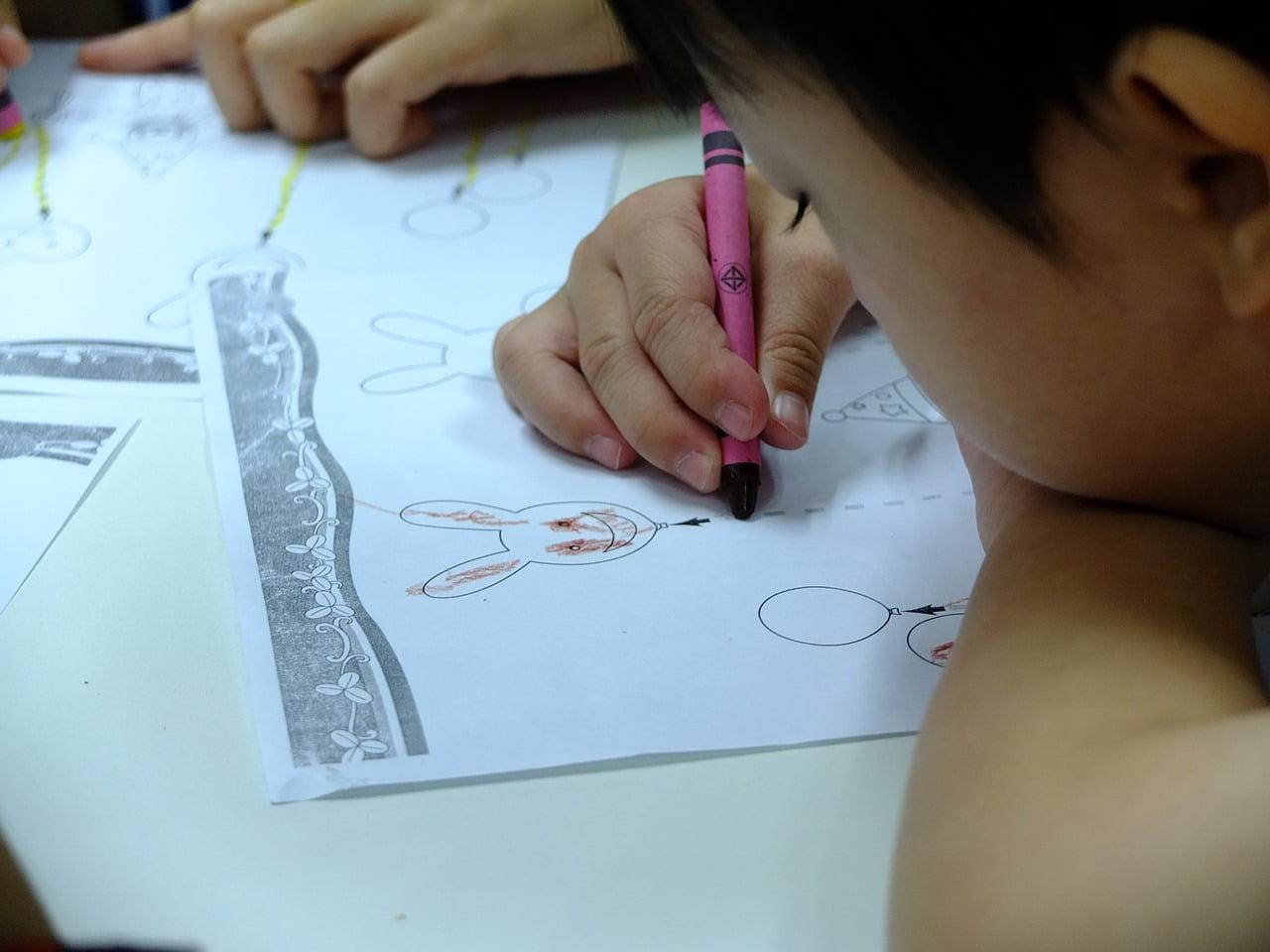 Chłopiec wykonuje ćwiczenia grafomotoryczne.