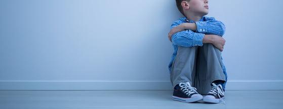 smutny chłopiec siedzi na podłodze