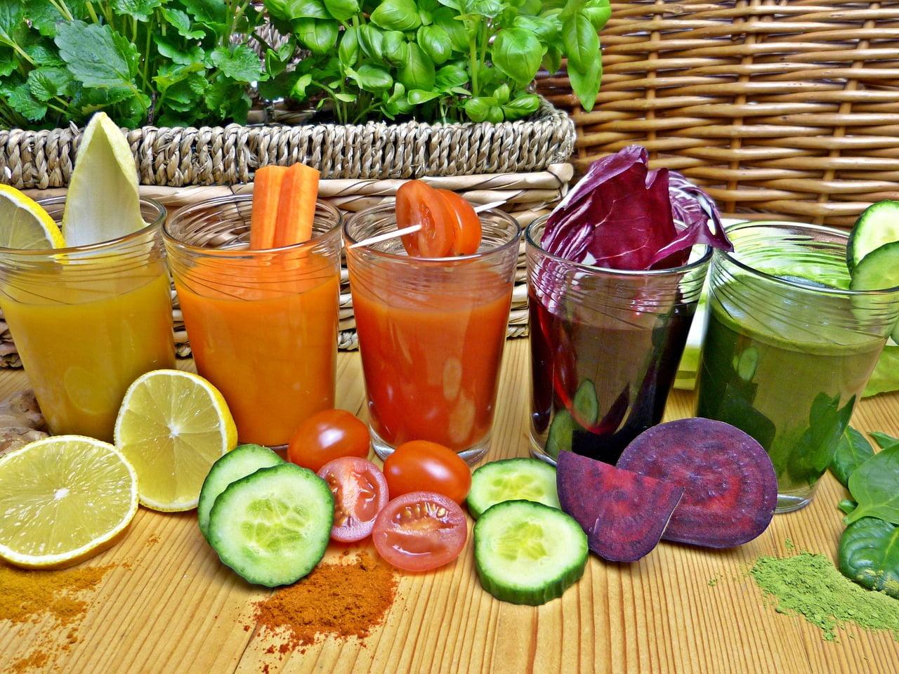 Ogórek, pomidor, kapusta czerwona, cytryna, obok szklanki z sokami warzywnymi