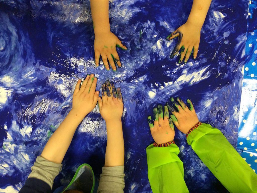 ręce dzieci majują fabami po kartonie