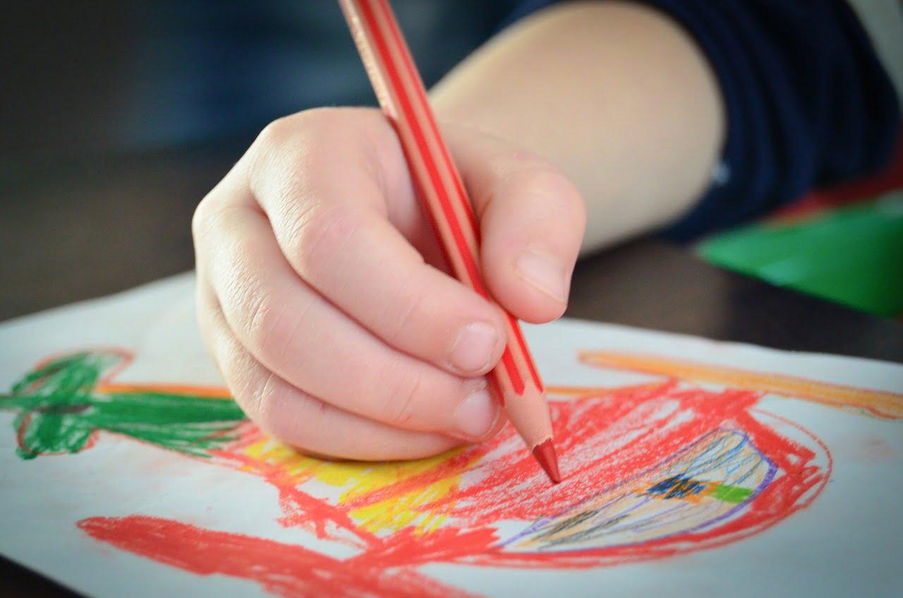 Ręka dziecka rysuje czerwoną kredką
