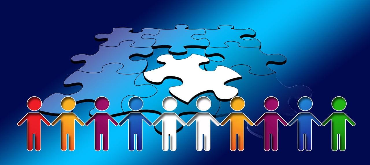 postacie ludzi trzymających się za ręce, w tle układanka z niebieskich puzzli i jeden biały puzzel