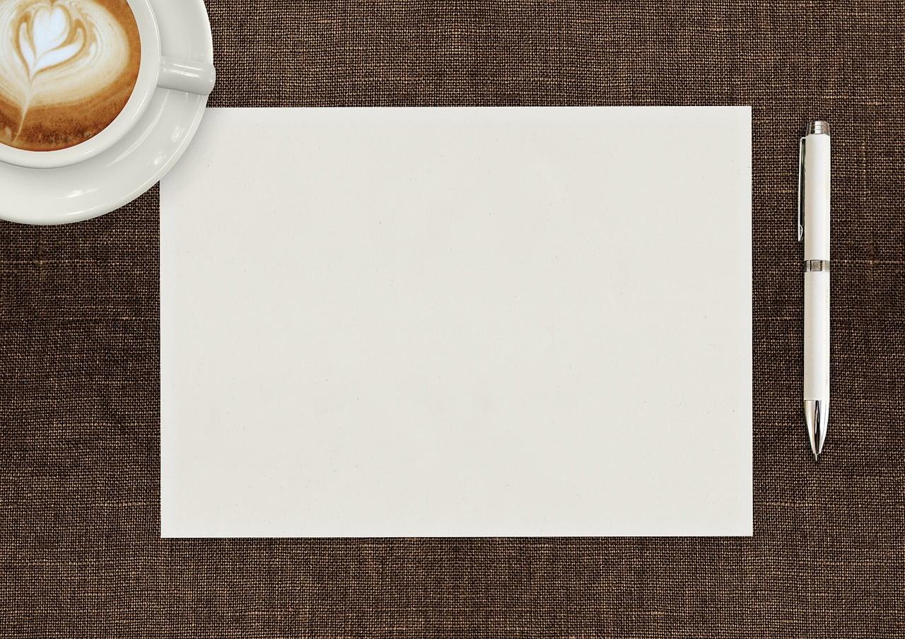 kartka papieru i długopis na stole, obok filiżanka kawy