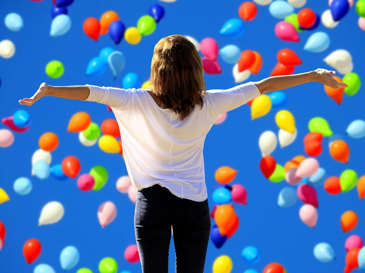 Dziewczyna z otwartymi ramionami stoi tyłem, wokół na tle nieba kolorowe balony