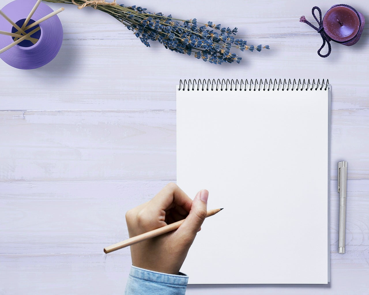 notatnik na stole, dłoń z ołówkiem pisze list, obok lawenda i świeca