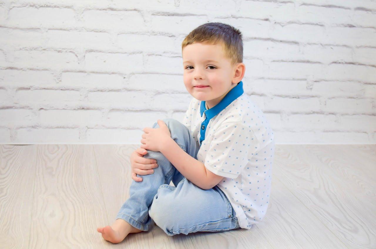 Chłopiec ok. lat 5, siedzi na podłodze.