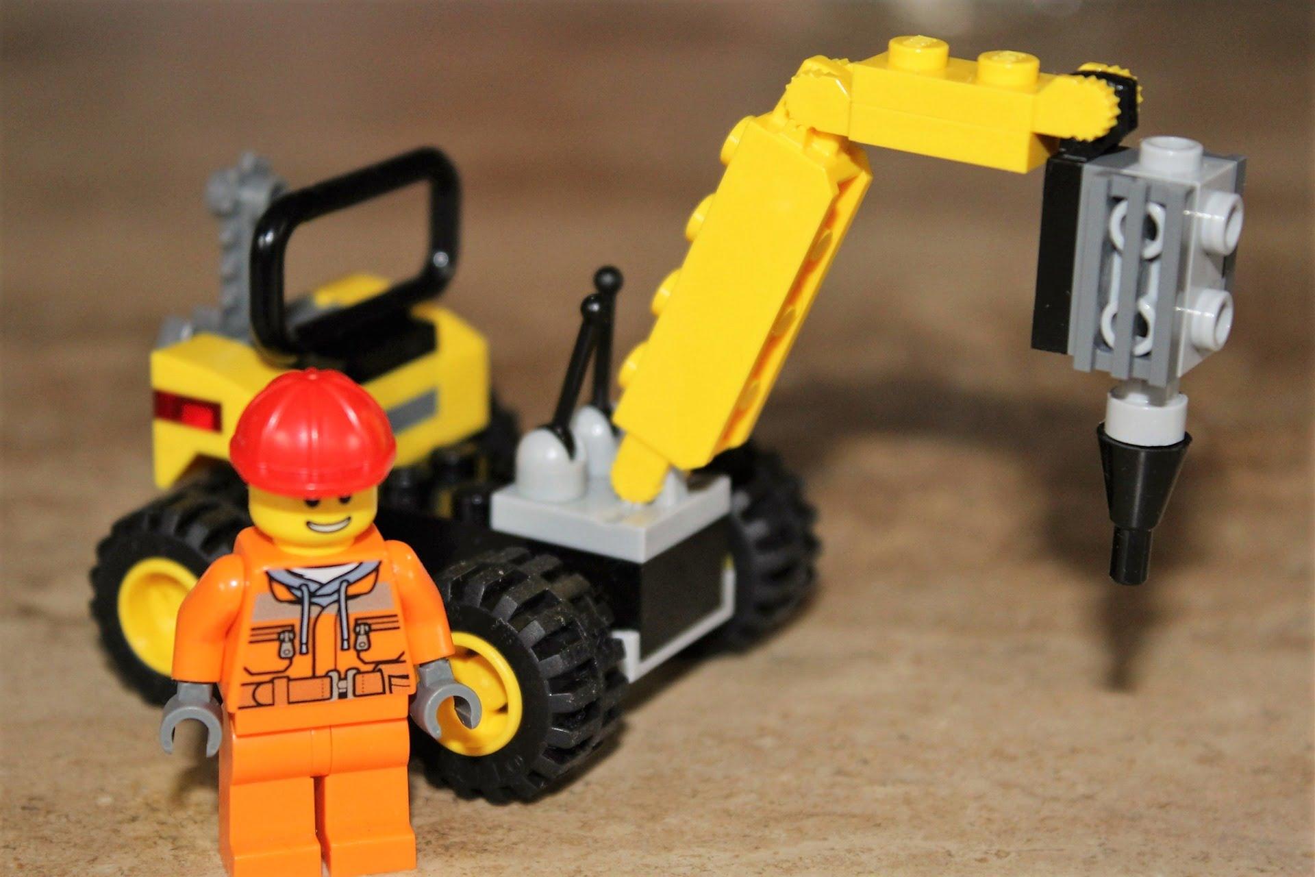 Dźwig z klocków lego, obok pracownik budowlany