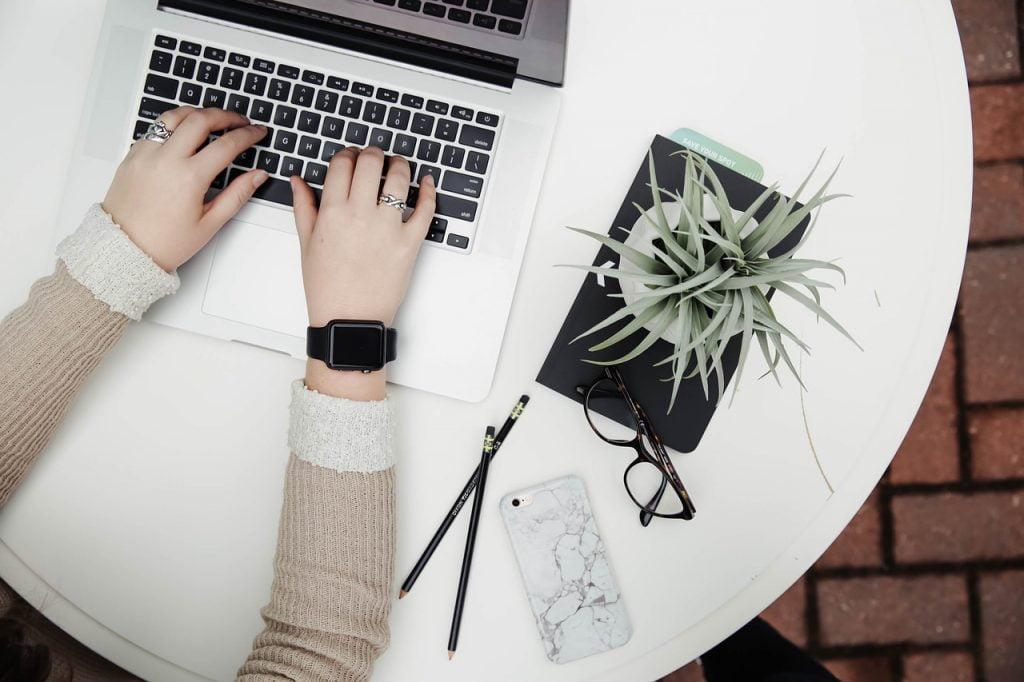 Widoczne ręce osoby piszące na klawiaturze komputera, obok na stole: okulary, ołówki, kwiatek w doniczce