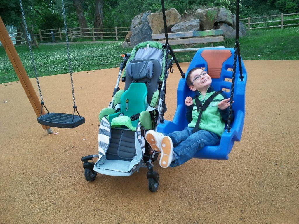 Niepełnosprawny chłopiec na placu zabaw na huśtwace