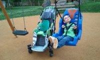 Niepełnosprawny chłopiec siedzi na huśtawce i uśmiecha się, obok niego stoi jego wózek