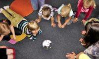 Grupa dzieci, które leżą na dywanie i bawią się - trening umiejętności społecznych