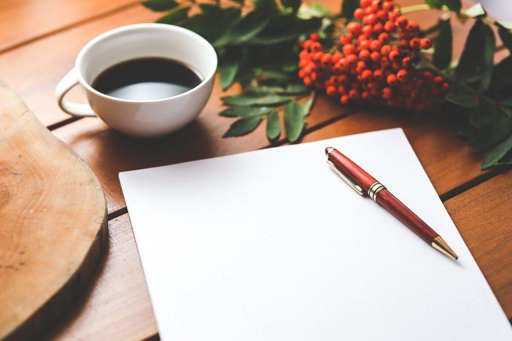 Kartka papieru, długopis na stole, obok filiżanka kawy i owoce jarzębiny