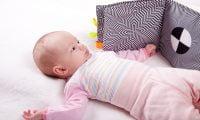 Małe dziecko patrzy na książeczkę sensoryczną