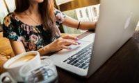Kobieta pracuje na laptopie, obok którego stoi kawa