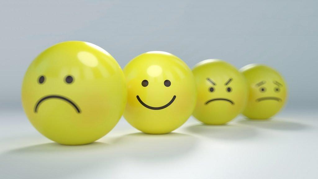 Żółte kule z narysowanymi emocjami: smutek, radość, złość