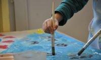 Rączka dziecka, które trzyma pędzel i maluje farbami