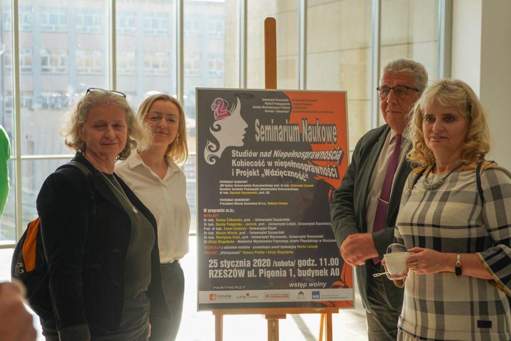 Uczestnicy seminarium Kobiecość w Niepełnosprawności przy plakacie wydarzenia