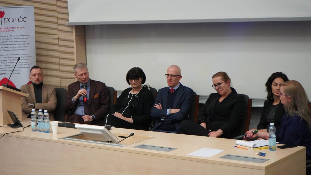 Naukowcy i wykładowcy siedzący za stołem podczas seminarium Kobiecość w Niepełnosprawności