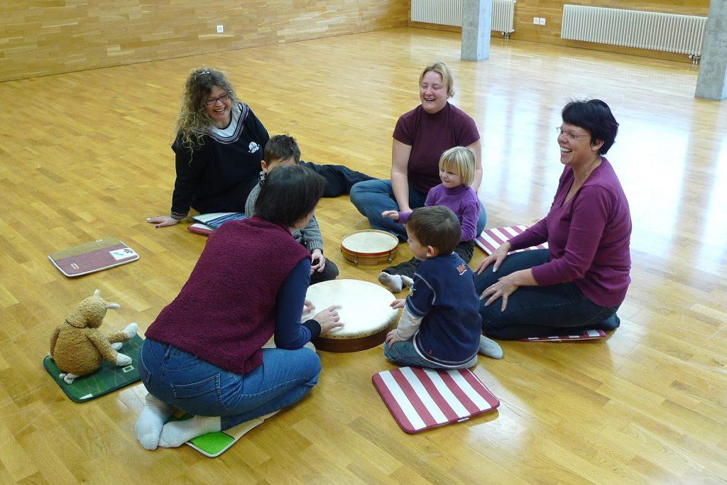 Muzykoterapeuta z dziećmi i rodzicami siedzą na podłodze i muzykują