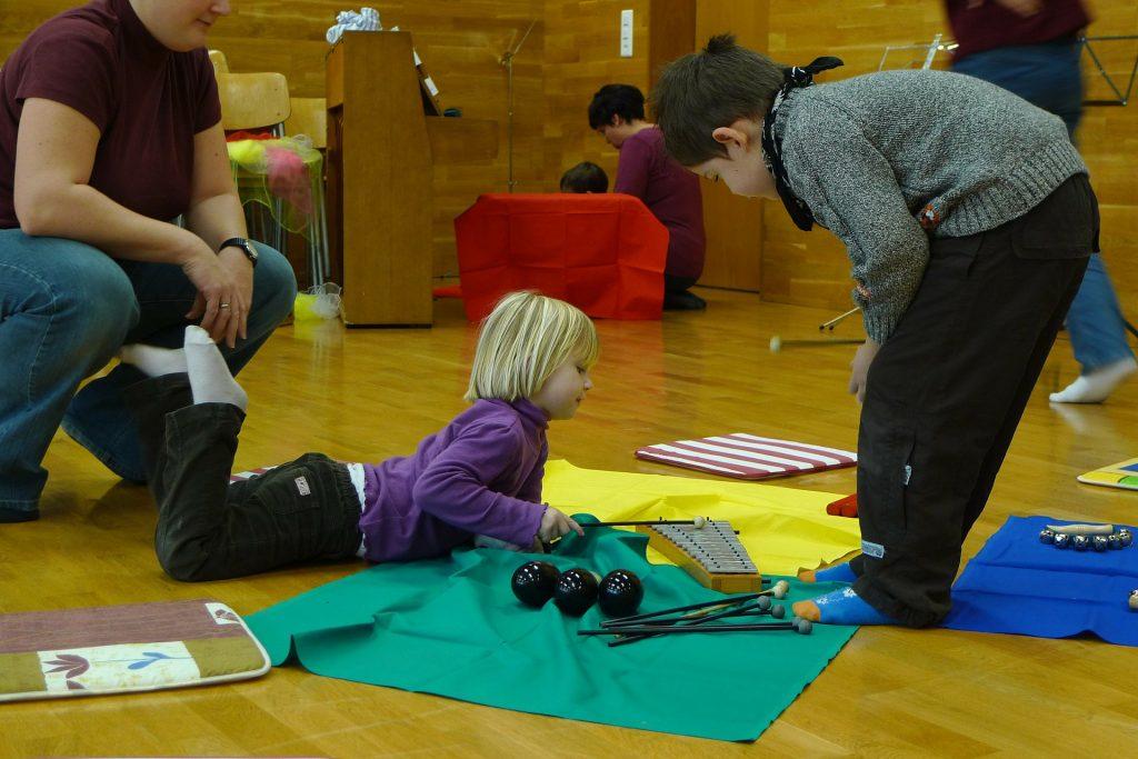 Muzykoterapeuta z dziećmi, dzieci zapoznają się z instrumentami: dzwonki, grzechotki