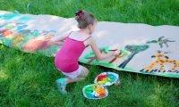 Dziewczynka malująca farbami na dużym papierze