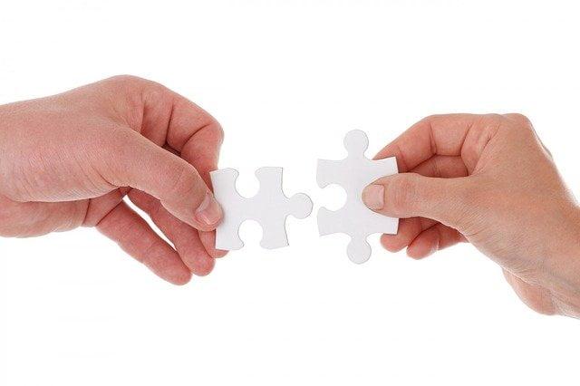 dwie ręce układające dwa puzzle